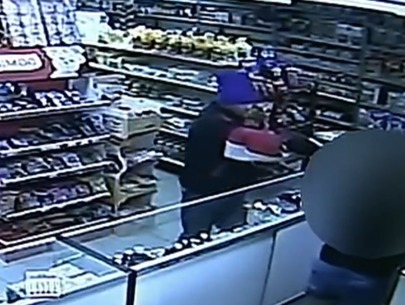 Video: Robber points gun at store clerk holding baby